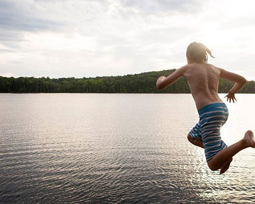 a young boy leaps into a cove