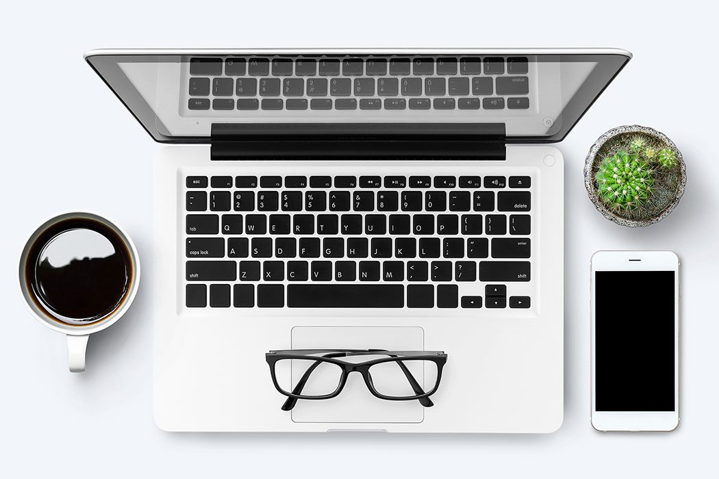 laptop with a pair of glasses, coffee much, cell phone and succulent on a white table