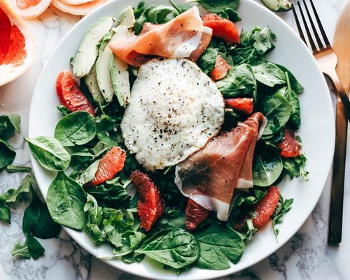breakfast salad with prosciutto and a fried egg