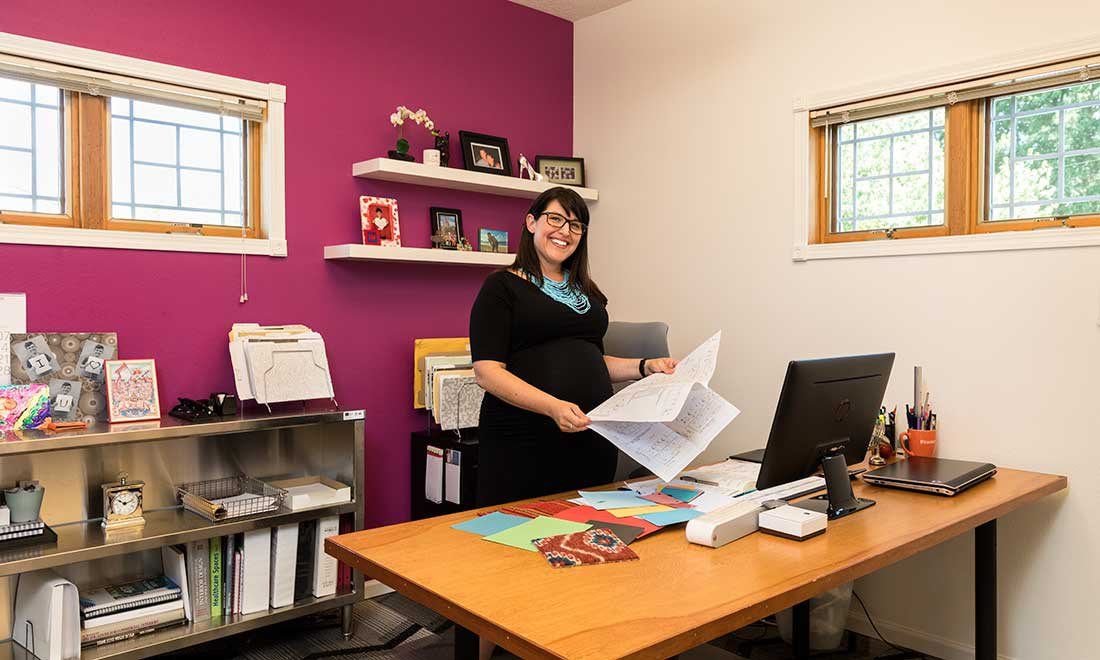 woman stands behind her desk smiling at the camera holding papers in her hand