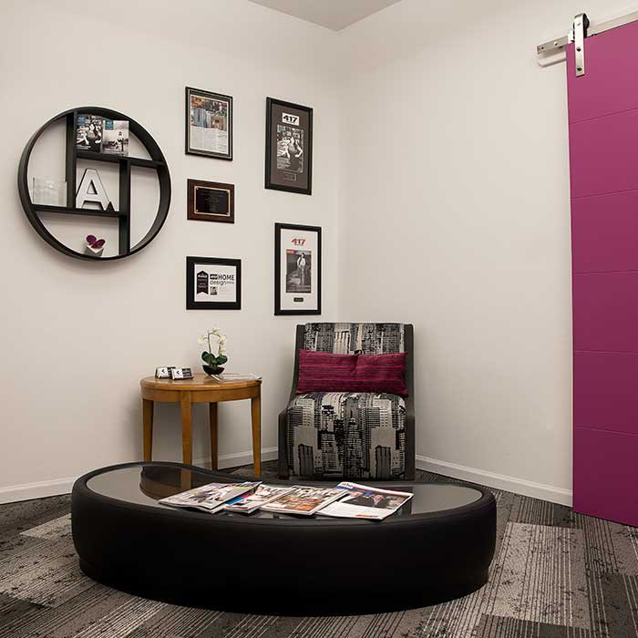 circular desk, chair, side table sit in the corner of the room with awards framed on the wall