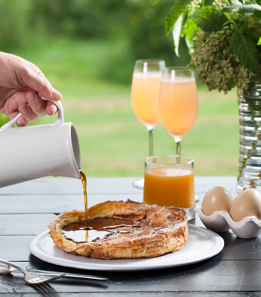 Pouring syrup on French toast with glasses of mimosas