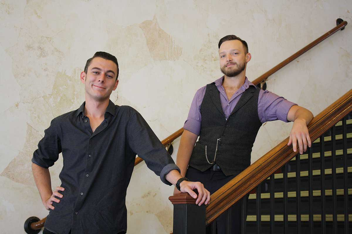 two man stand on a staircase smiling and posing at the camera