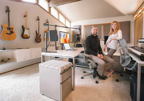 Phil sits and Chastin stands in their clean office room; guitars line the walls