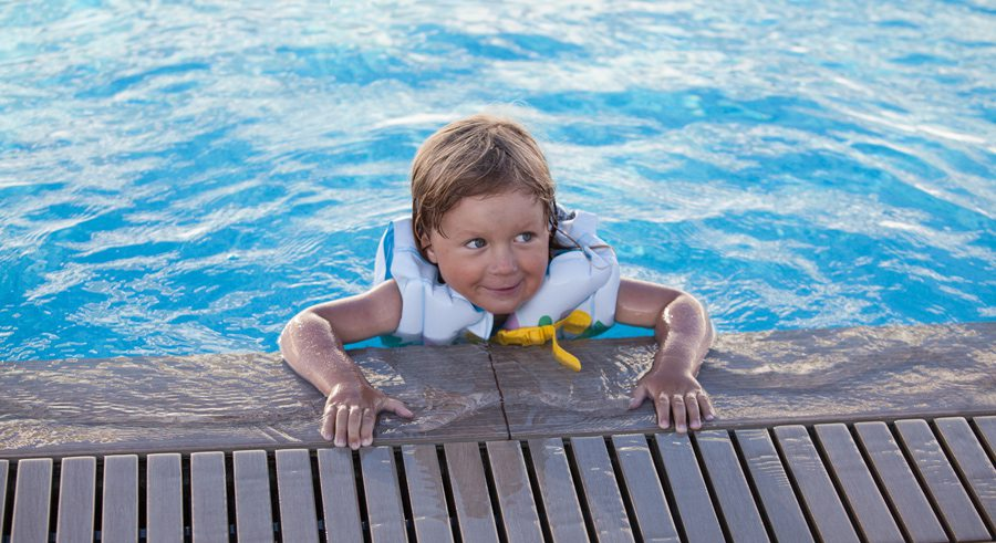 Kid in pool wearing lifejacket