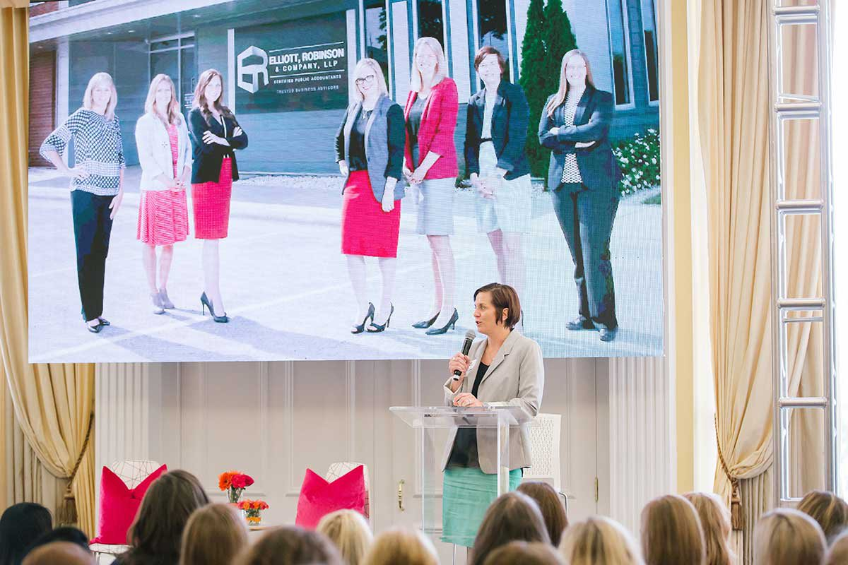 Amanda presents in front of a crowd at Ladies Who Launch event