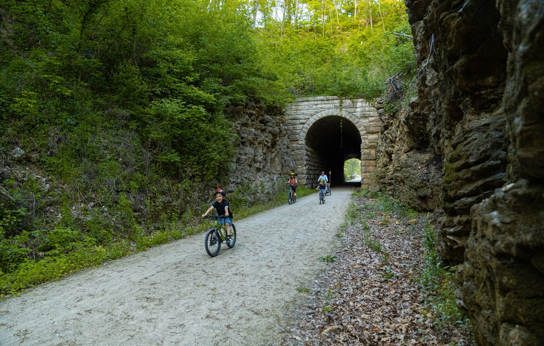 family rides bikes through tunnel on bike trail