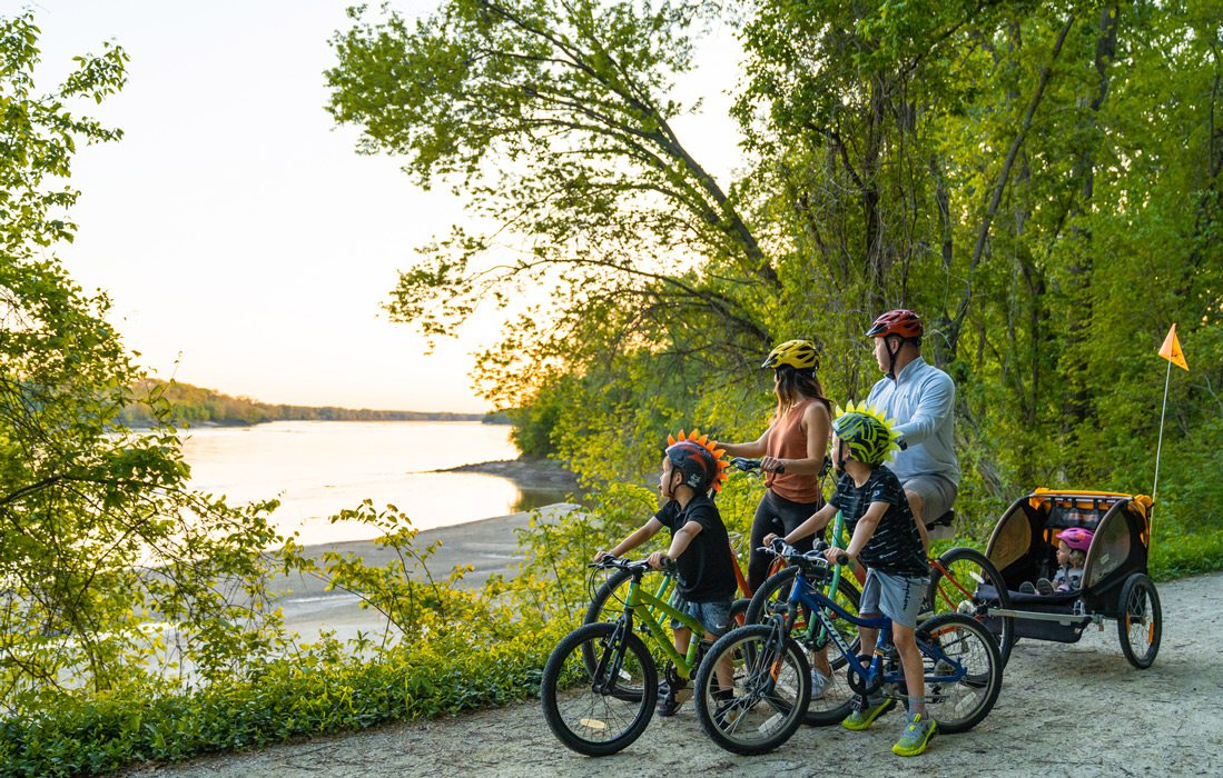 Family of five on bikes stop to look at lake