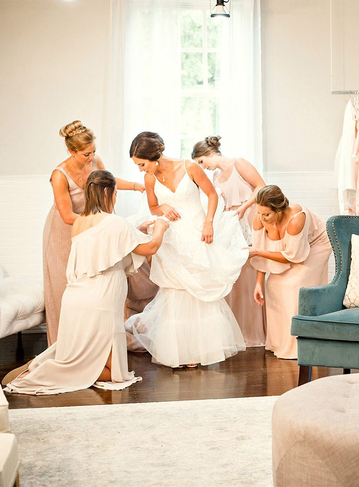 Bridesmaids helping the bride get ready for her wedding