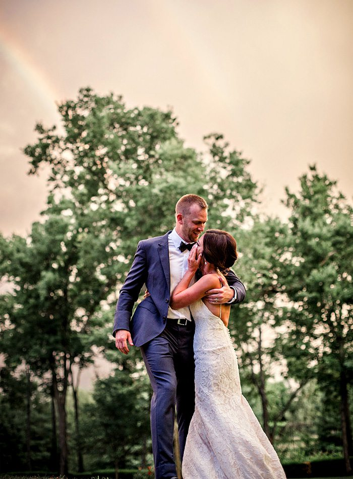 wedding couple standing in front of a rainbow