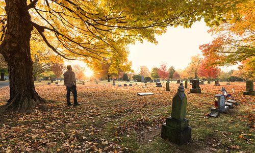 man standing in maple cemetery during fall