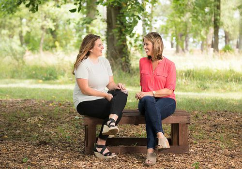 Jody and Julie sit on a bench speaking in a park