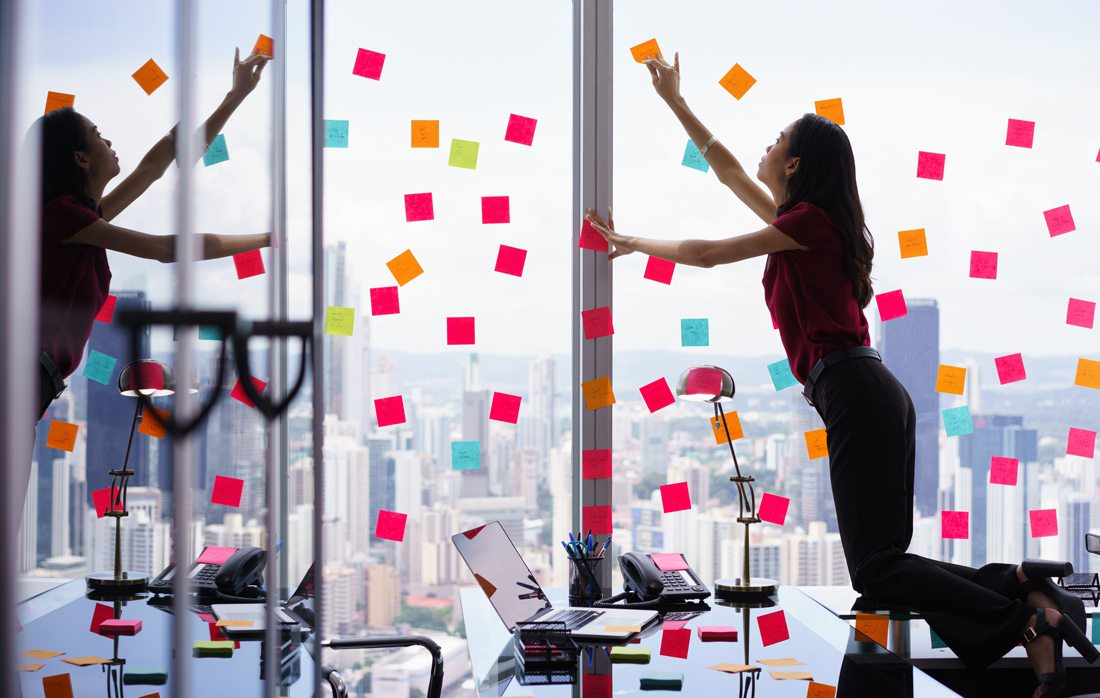 Woman working in skyscraper, putting sticky notes on windows.