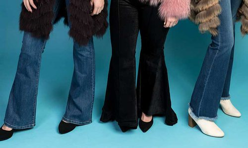 legs of three women wearing bell bottom jeans and booties