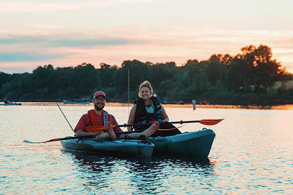 A man and a woman smile at the camera while floating in their kayaks