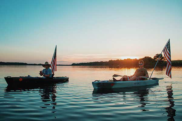 Two men sit in their boats with the sun setting past the water behind them