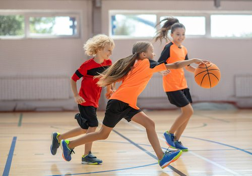 Stock photo of kids playing basketball indoors