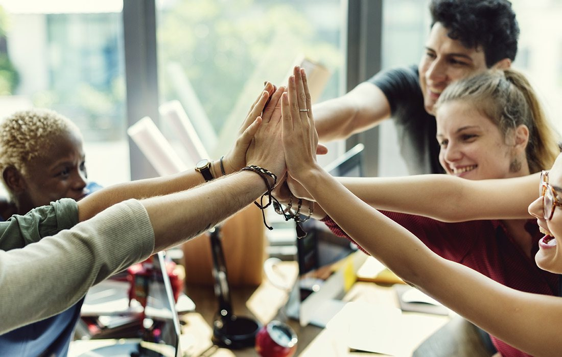 Team high fiving in office