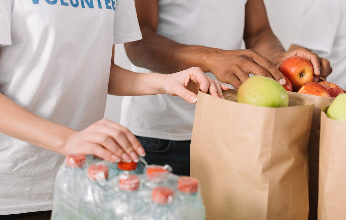 Stock image of volunteers with food donations