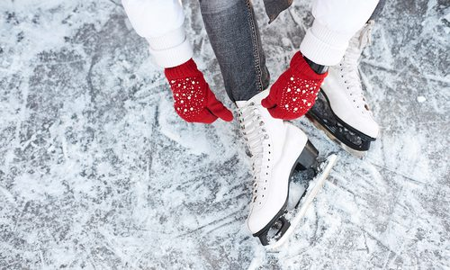 Lacing up ice skates with red gloves