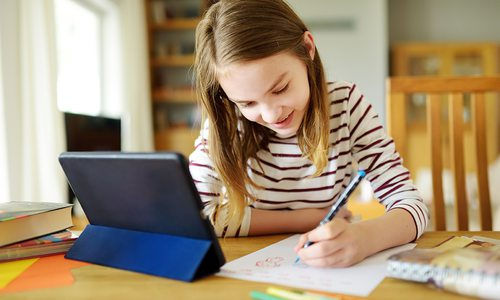 Stock image of young girl taking an online class