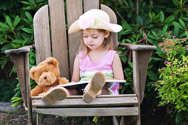 Stock photo of little girl reading outside