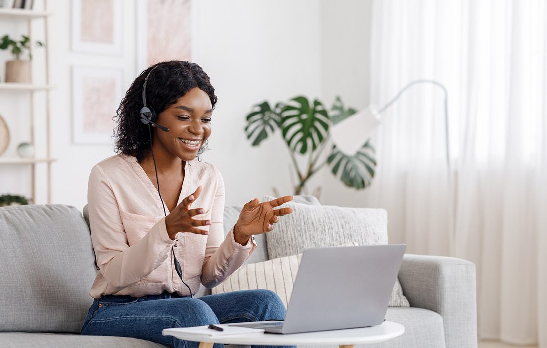 Woman talking on headset with laptop