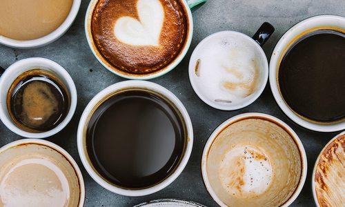 A barista pours milk into a cappuccino