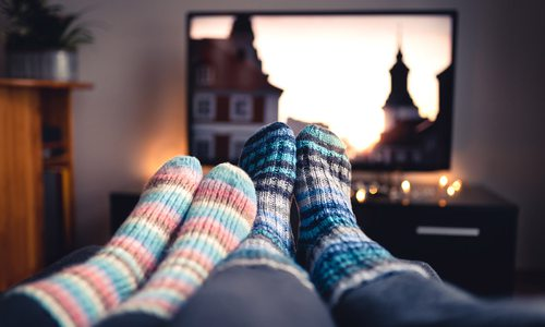 Couple streaming TV together stock photo.