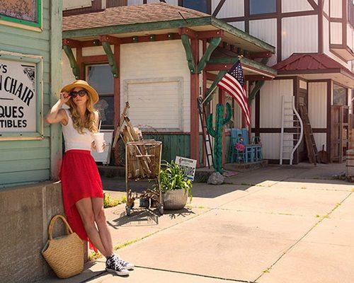 a woman leans against a store front