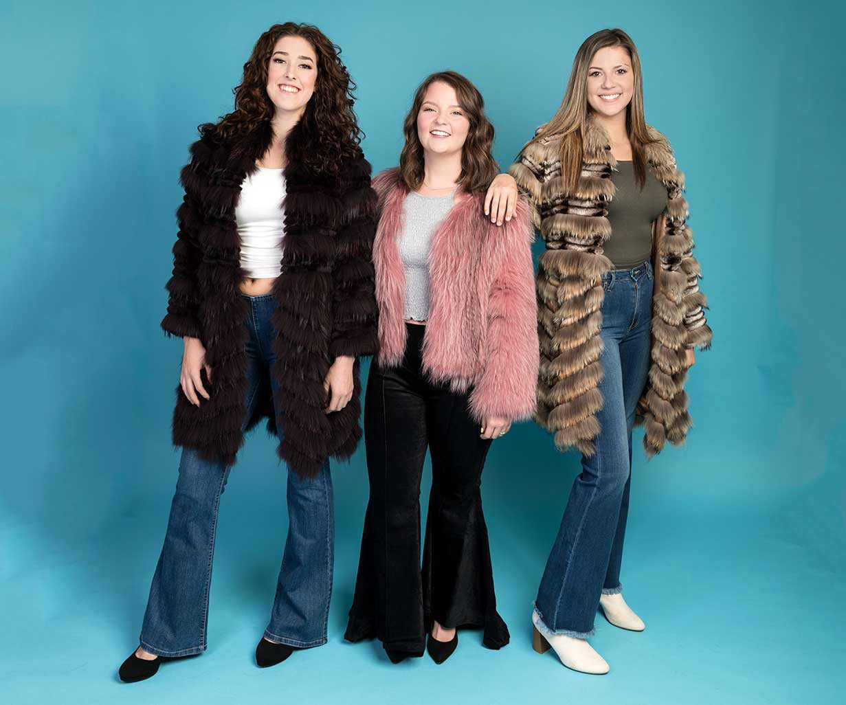 three women wearing midriff tops, furs, bell bottom jeans, and booties