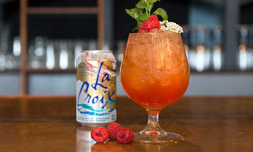the aperol spritz with a can of La Croix and raspberries next to it