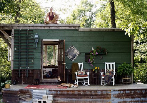 Jayme sits on top of the tiny home, her dog lounges on the base