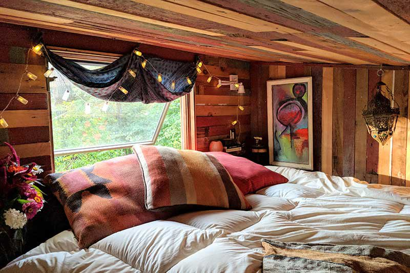 the bed is lofted with a low ceiling and a window at the head