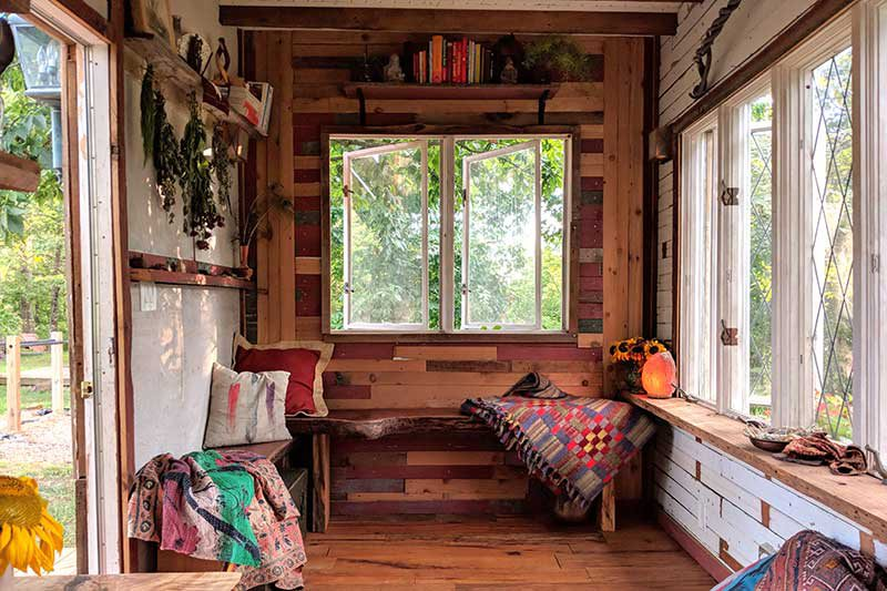 the bottom floor of the tiny home featuring several windows and sitting areas along the walls of the room