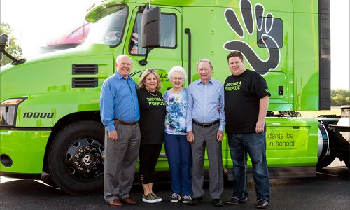 people standing in front of a bright green semi truck