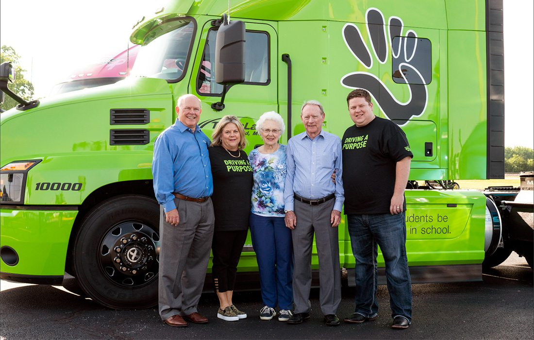 people standing in front of lime green semi
