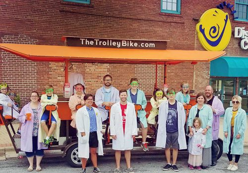 the Trolley Bike staff and Discover Center friends line up in front of the trolley bike parked outside the Discovery Center