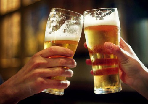 two people cheersing two pints of beer