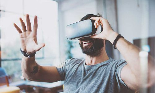 A man places a hand in front of his face as he looks through virtual reality googles