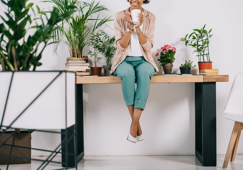 Woman sitting on desk with office plants