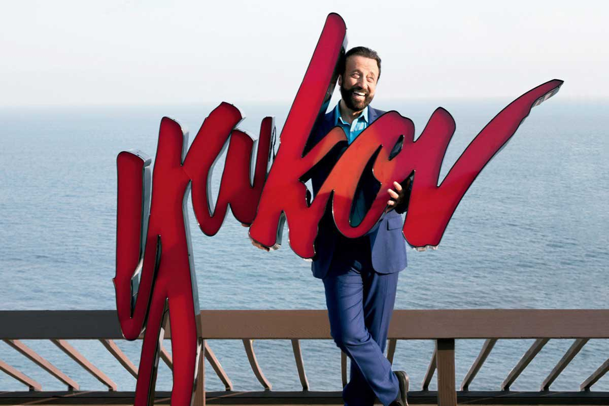 "Yakob stands on a pier, water behind him, holding a large sign with his name on it: ""Yakov"""
